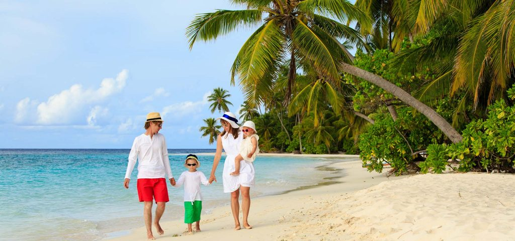Family with two kids walking at tropical beach, family beach vacation