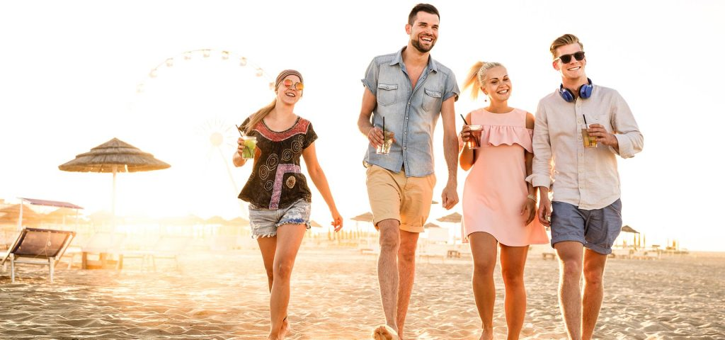 Summer vacations and friendship concept with young people millennials walking at beach Miami