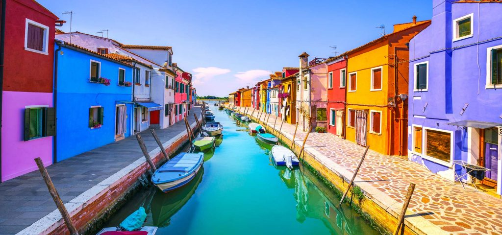 Burano island canal - colorful home and boats, Italy
