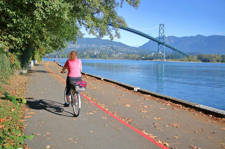 A cyclist travels on the Stanley Park seawall in in Vancouver, BC