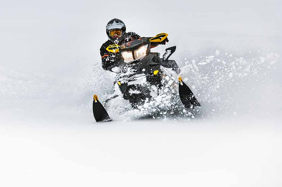 In deep snowdrift snowmobile rider make fast turn.