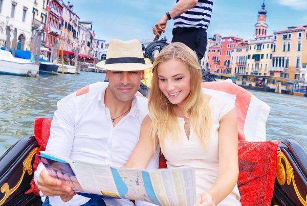 Couple traveling to Venice and riding on a gondola on the Grand Canal and searching something on Map