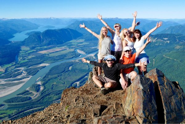 Group of Happy Travelers on Mountain Top, Cheering.
